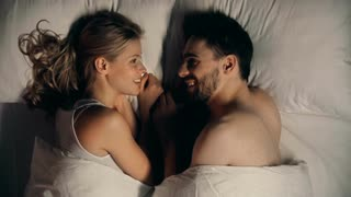 close-up-of-young-couple-lying-in-bed-facing-each-other-and-talking_nyitj6x_m__S0000